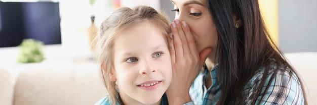 Maman murmure un secret à l'oreille d'une petite fille