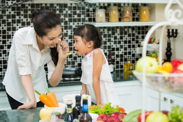 Maman nourrit bébé drôle à la maison