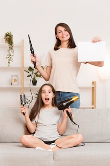 Maman ondulant les cheveux de la fille à la maison
