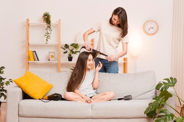 Maman ondulant les cheveux de la fille