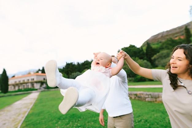 Maman et papa balancent la petite fille par les bras dans le jardin vert villa milocer monténégro