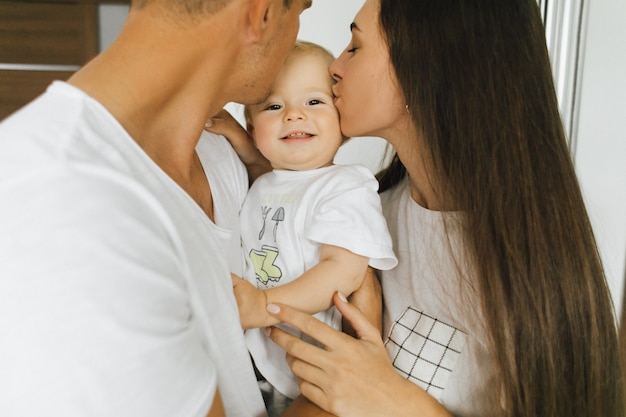 Maman et papa embrassent leur petit fils. l'enfant se réjouit.