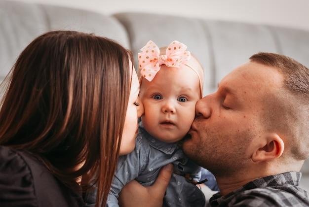 Maman et papa embrassent leur petite fille dans la joue. portrait de famille en gros plan