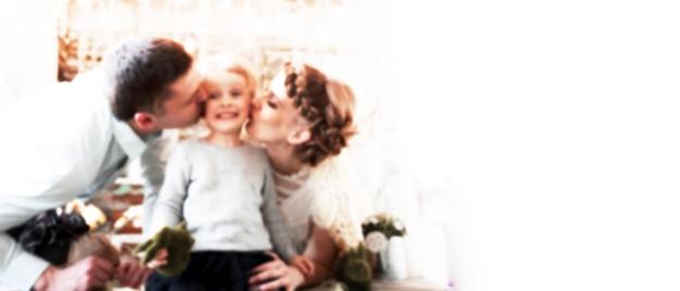 Maman et papa embrassent sa petite fille. image floue pour le texte publicitaire. photo avec espace copie