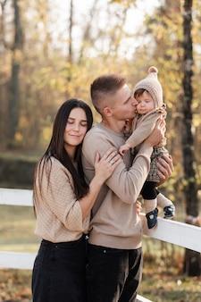 Maman papa étreignant sa fille et s'embrassant dans le parc en automne