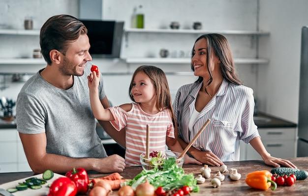 Maman, papa et fille cuisinent dans la cuisine. concept de famille heureuse. bel homme, jolie jeune femme et leur petite fille mignonne font de la salade ensemble. mode de vie sain.