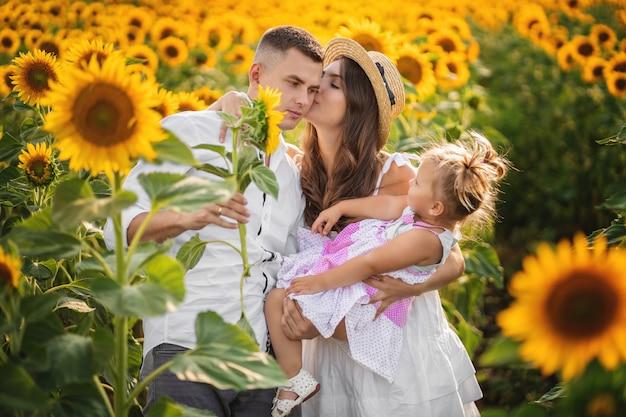 Maman, papa et fille enfant en bas âge, marchez dans le champ. heureuse jeune famille, passer du temps ensemble, à l'extérieur, en vacances, à l'extérieur. le concept de vacances en famille.