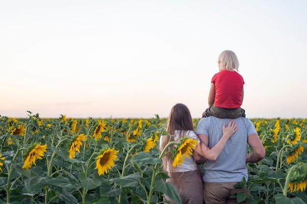 Maman, papa et fils sur champ de tournesol