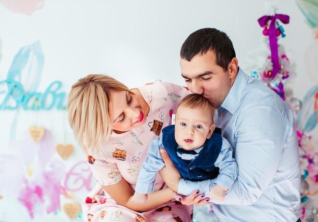 Maman, papa et leur petit fils posent dans la chambre avec un arbre de noël rose