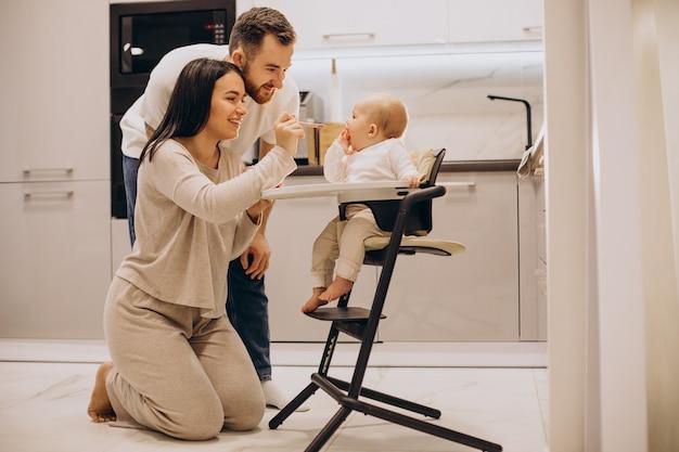 Maman avec papa nourrit leur petite fille dans une chaise d'alimentation