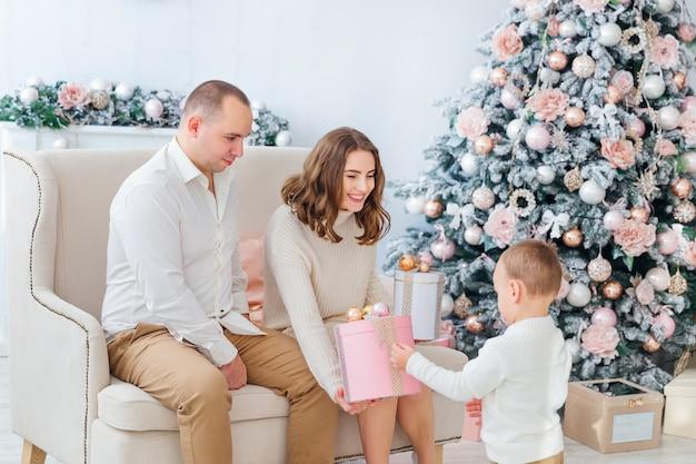 Maman et papa ouvrent des cadeaux avec leur fils