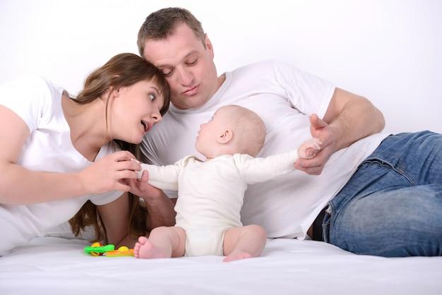 Maman et papa avec un petit enfant sur le lit.