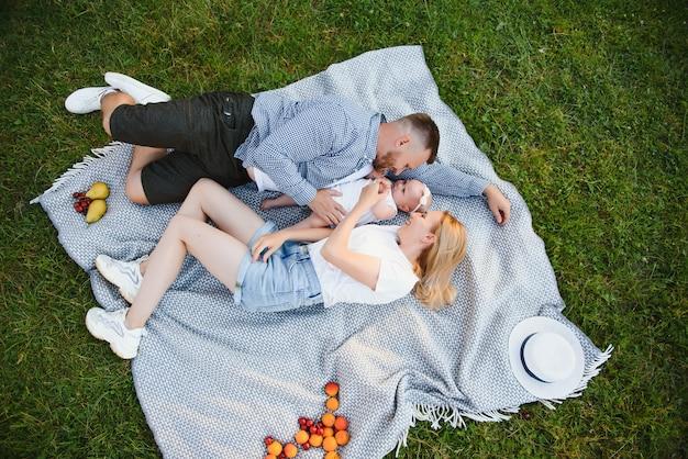 Maman, papa et petit fils allongés sur la couverture dans le parc d'été. le concept de vacances d'été. fête des mères, des pères, des bébés. famille passant du temps ensemble sur la nature. regard de famille