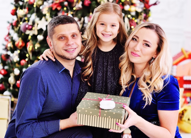 Maman, papa et petite fille s'embrassant avec un cadeau à la main sur le fond d'un sapin de noël.