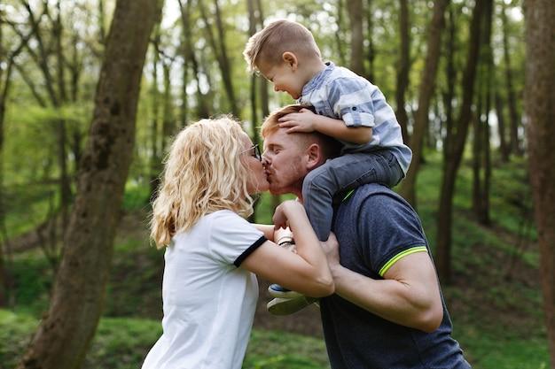 Maman et papa s'embrassent pendant que leur petit fils ferme les yeux