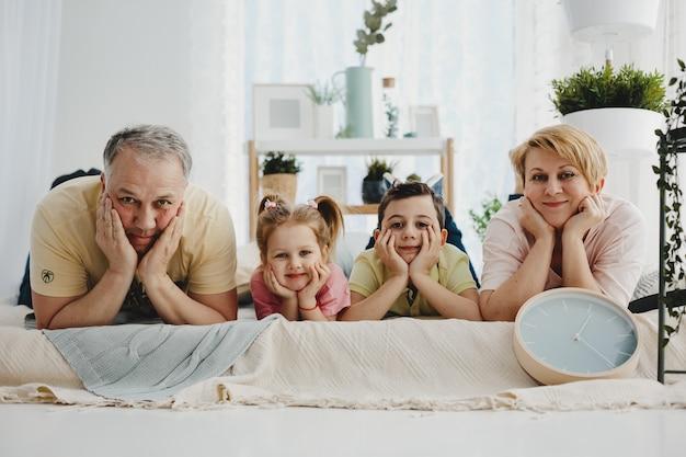 Maman et papa se trouvent avec leurs enfants dans les mêmes poses sur le lit