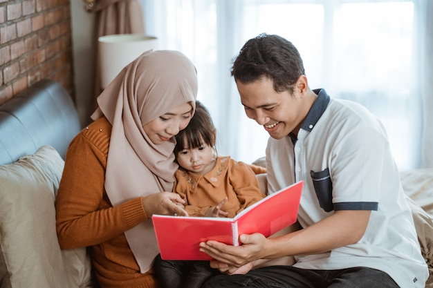 Maman et papa sourient tenant un livre quand ils voient un livre d'histoire avec leur fille