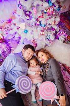 Maman et papa tiennent de grands bonbons roses couchés avec leur fille sur le sol