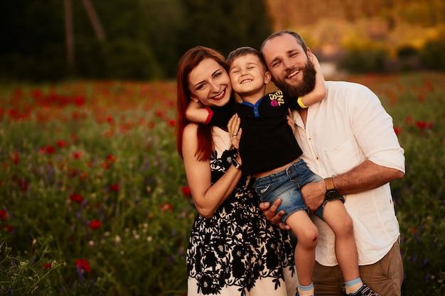 Maman et papa tiennent leur petit fils sur les bras debout sur le champ vert avec des coquelicots