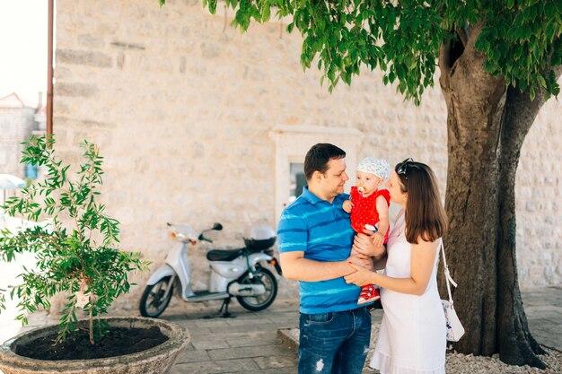 Maman et papa tiennent une petite fille dans une robe rouge et avec une tétine dans leur bouche dans leurs bras