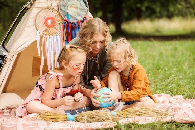 Maman passe du temps avec ses petites filles, leur apprenant la géographie de manière ludique.