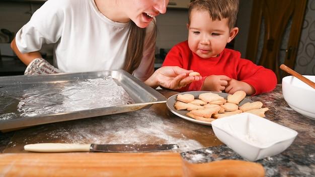 Maman et petit fils font cuire des biscuits de noël ensemble