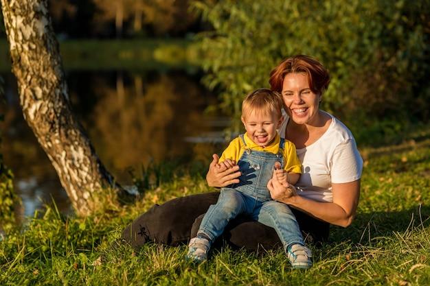 Maman et petit garçon s'asseoir sur la rive du fleuve dans les rayons du soleil couchant un soir d'automne