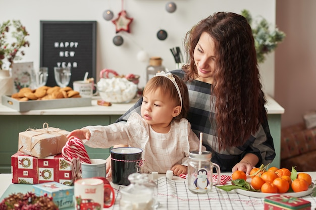 Maman et petite fille dans la cuisine décorée pour le nouvel an et noël