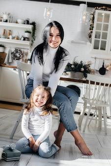 Maman avec une petite fille déballe des cadeaux. vacances.