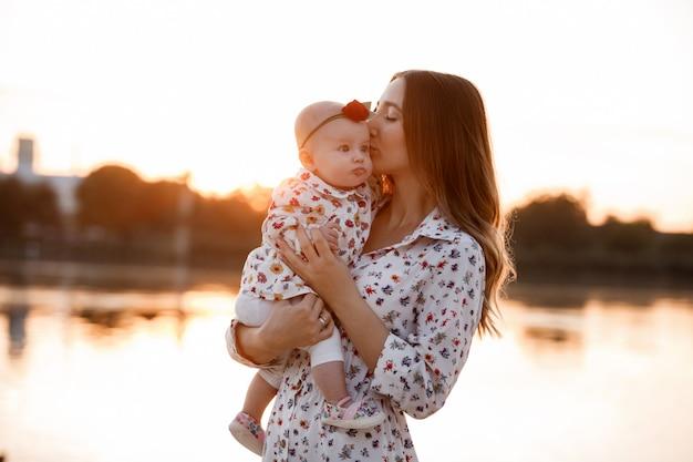 Maman, petite fille à l'extérieur. jeune maman avec bébé femme marche sur la plage près du lac au coucher du soleil. vacances en famille sur étang. portrait maman avec enfant ensemble dans la nature.