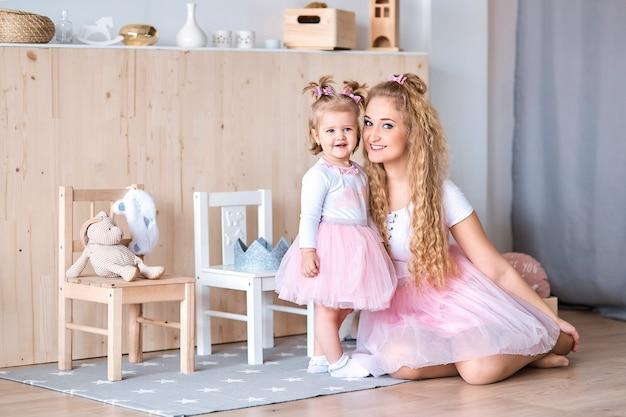 Maman et petite fille en jupes roses font des câlins à la maison