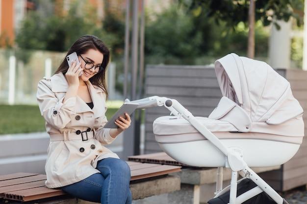 Maman pigiste réussie travaillant avec un téléphone, assise sur un banc près de la poussette de bébé dans le parc.