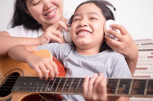 La maman portait des écouteurs blancs pour la petite fille