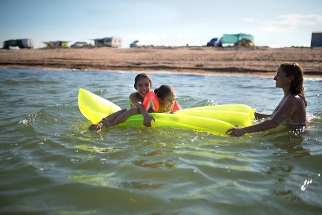 Une maman positive se détend en mer avec ses deux petites filles par une journée d'été ensoleillée. le concept de vacances d'été en mer et de vacances d'été