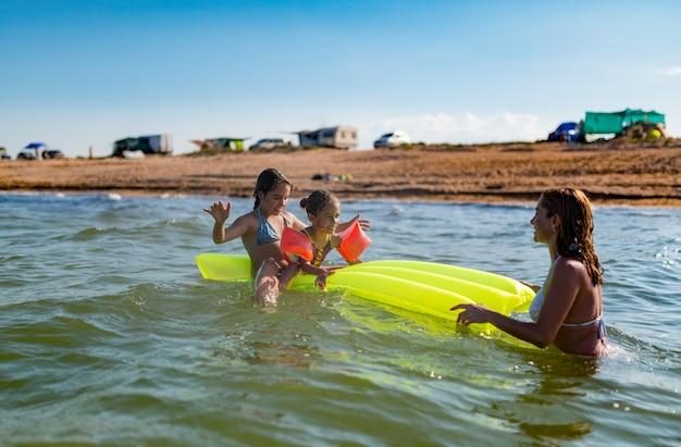 Une maman positive se détend en mer avec ses deux petites filles par une journée d'été ensoleillée