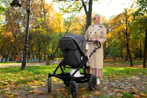 Maman avec poussette se promène dans le parc