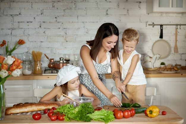 Maman prépare le déjeuner avec les enfants. une femme apprend à sa fille à cuisiner avec son fils. végétarisme et alimentation saine et naturelle