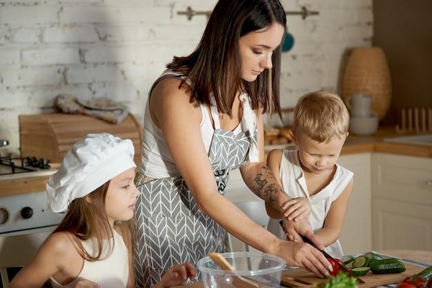 Maman prépare le déjeuner avec les enfants. une femme apprend à sa fille à cuisiner avec son fils
