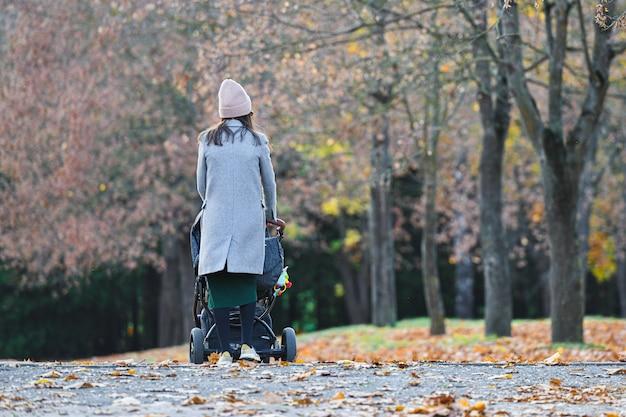 Maman qui marche avec une poussette dans un parc d'automne