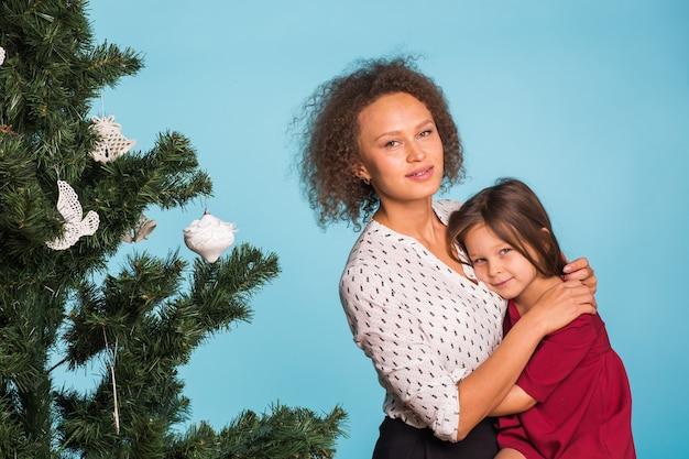 Maman de race mixte et sa fille avec arbre de noël sur fond bleu
