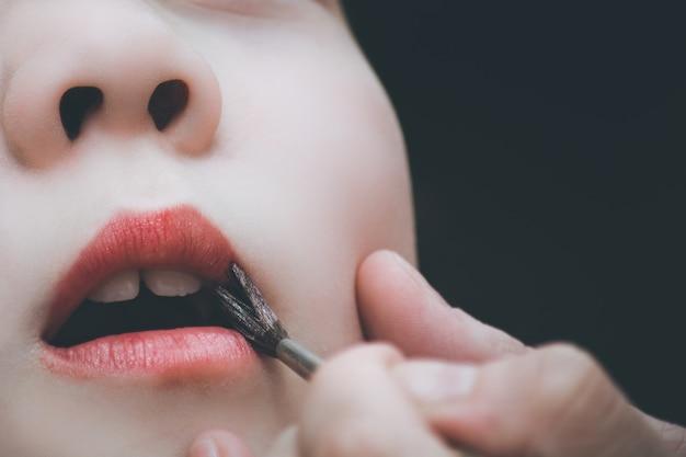 Maman rouge à lèvres pour la séance photo à la maison
