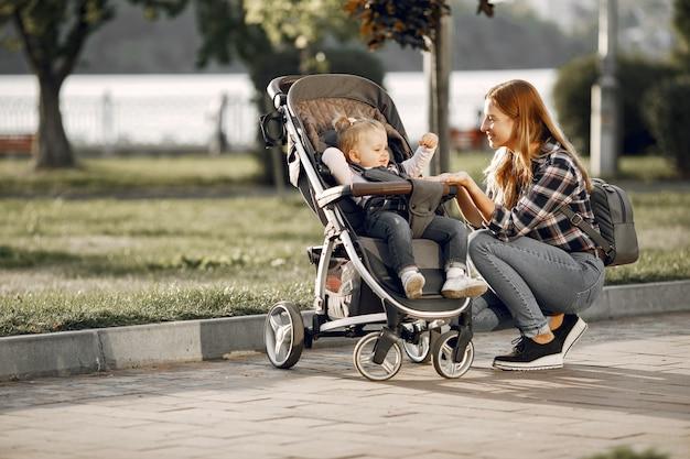 Maman sur la rue de la ville. femme avec son enfant assis dans un landau. concept de famille.
