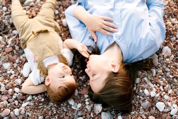 Maman s'allonge avec son petit-fils sur la plage de galets et joue avec lui