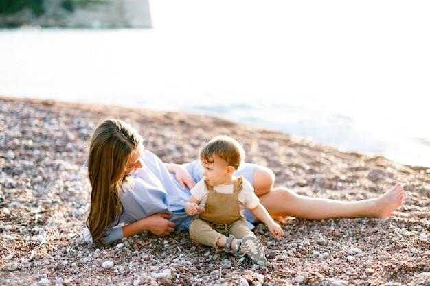 Maman s'allonge avec son petit fils sur la plage de galets près de l'eau et joue avec lui