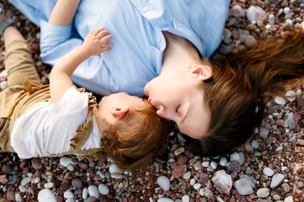 Maman s'allonge avec son petit fils sur la plage de galets
