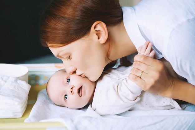 Maman s'occupe doucement de bébé sur la table à langer à la maison mère et enfant nouveau-né le plus mignon souriant