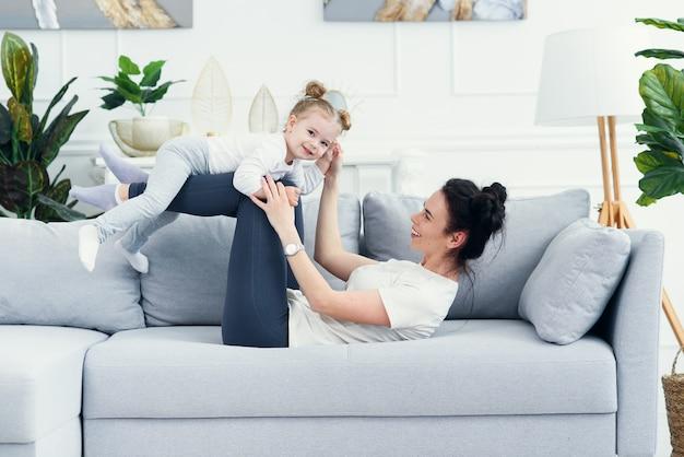 Maman et sa fille allongées sur le canapé dans le salon.