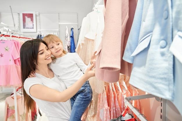 Maman et sa fille choisissent des vêtements pour enfants.
