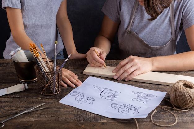 Maman et sa fille créent ensemble un jouet pour arbre de noël. fond gris. symbole du rat du nouvel an.