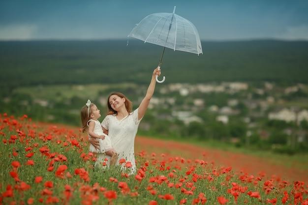 Maman avec sa fille dans un champ avec des coquelicots tient sa fille et un parapluie transparent dans ses mains
